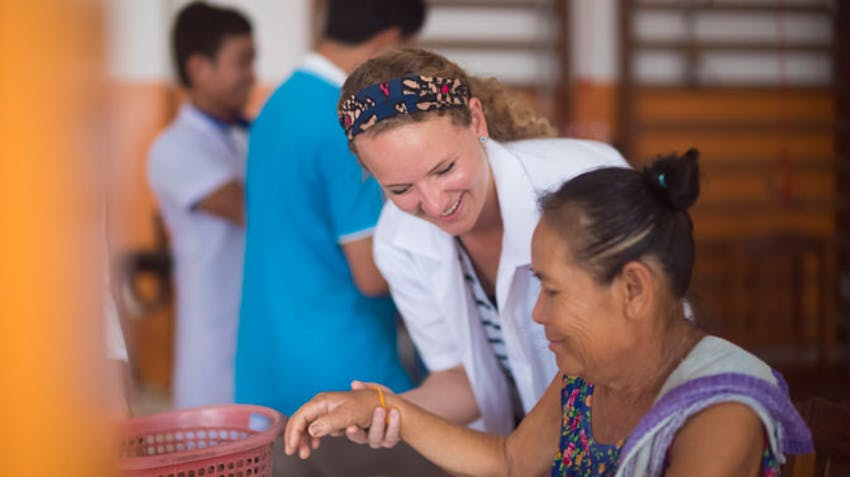 A medical volunteer helps a patient in Laos with IVHQ