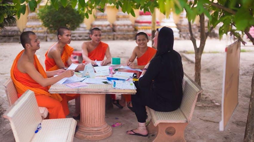 An IVHQ volunteer teaching monks in Laos