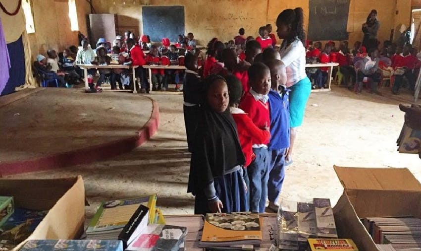 Michael Hobbs giving out pencils and workbooks to Blessed Hope children