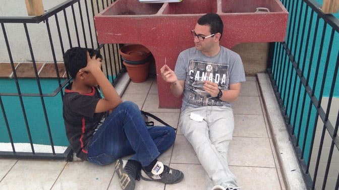 IVHQ teach and volunteer abroad scholarship winner, Armando, with a student