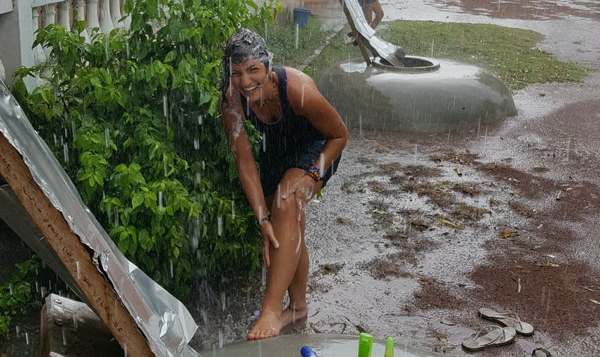 IVHQer Lara showers in the rain while volunteering in Ghana