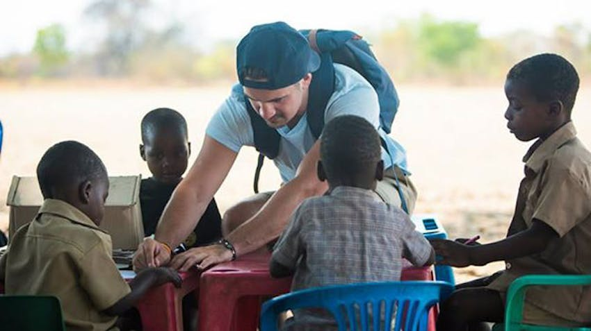 An IVHQ volunteer teaches children in Victoria Falls