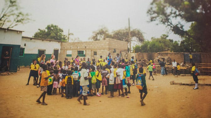 Volunteers sing with students at a school in Zambia with IVHQ