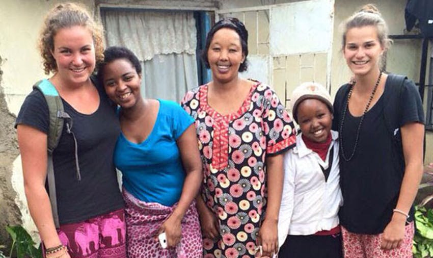 IVHQ volunteers with their host family in Tanzania with IVHQ