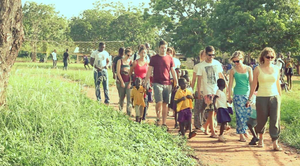 Volunteers walking with local children in Ghana