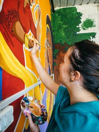 Childcare volunteer painting in Delhi India with IVHQ