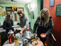 Volunteers serving dinner in Dharamsala, India with IVHQ
