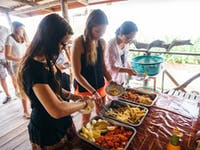 IVHQ volunteers serve a meal in Laos