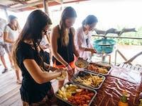 IVHQ volunteers serve a meal in Laos