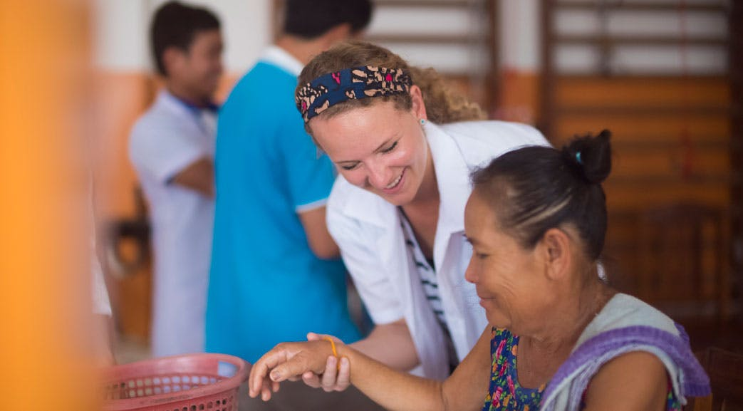 A medical volunteer works on a patient on the IVHQ Laos program