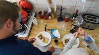 Volunteer preparing meal in Romania with IVHQ