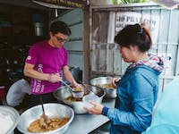 Volunteer serving food on the Food Outreach volunteers with IVHQ in Vietnam
